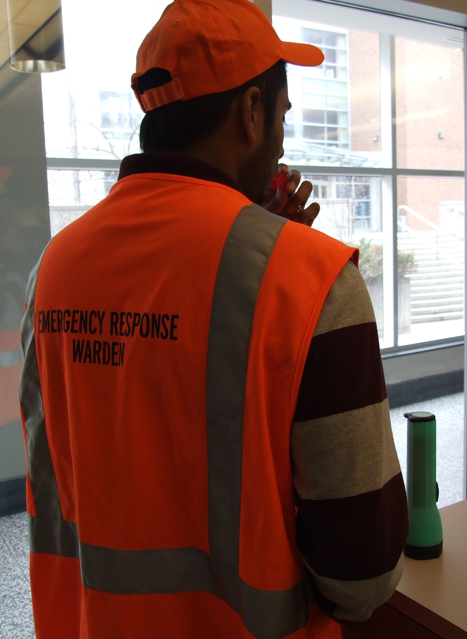 A Person with an Orange Vest Displaying Emergency Response Warden blowing a whistle